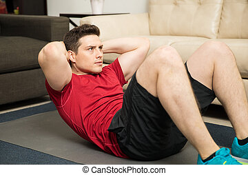 Athletic man doing crunches at home
