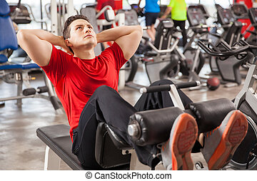 Athletic man doing crunches in a gym