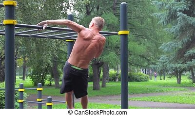 Athletic man doing gymnastics elements in City Park