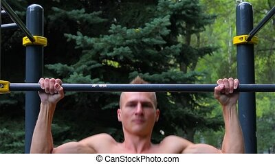 Athletic man doing pull ups on horizontal bar in City Park. front view. Workout.