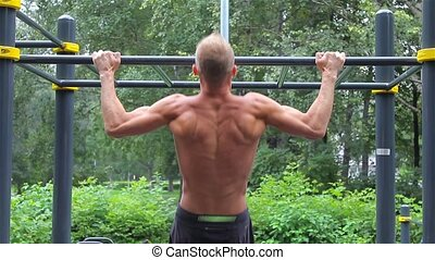 Athletic man doing pull ups on horizontal bar in City Park. rear view. Workout.