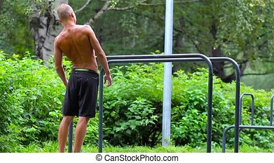 Athletic man doing warm-up before exercise on bars in City Park under summer trees for sport fitness