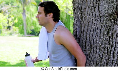 Athletic man drinking water while leaning against a tree