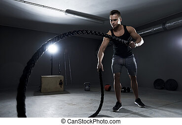 Athletic man efforting on crossfit training with ropes