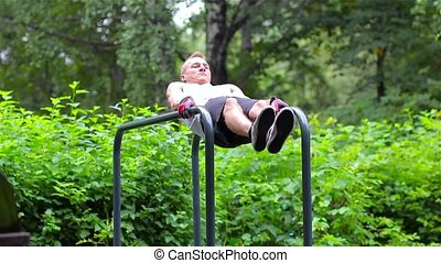 Athletic man exercise the abdominals on bars in City Park under summer trees for sport fitness. abs