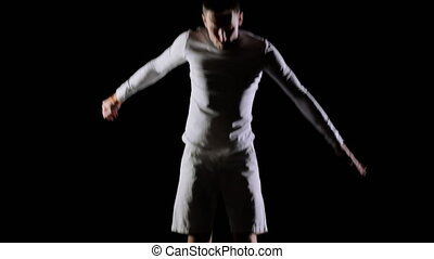 Athletic man in white clothes performs tricks jumping on a...