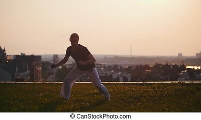 Athletic man in white pants trains capoeira on the grass, sunset, slow motion