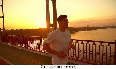 athletic man jogging during sundown