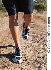 Athletic man jogging in the country
