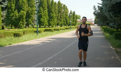 Athletic man jogging in the park and checking smart phone...