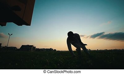 Athletic man performs elements of capoeira dance on the grass, summer evening, silhouette