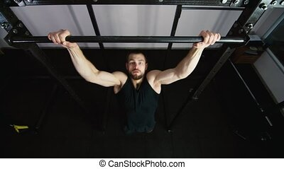 Athletic man pulled on the bar top view