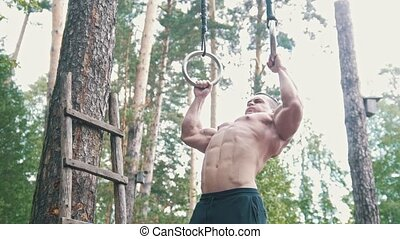 Athletic man pulled up on the rings in the forest