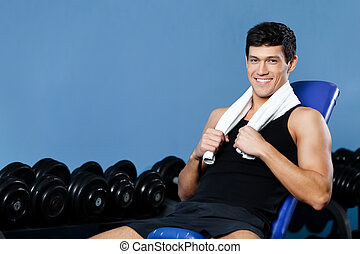Athletic man rests in gym - Athletic man rests sitting on...