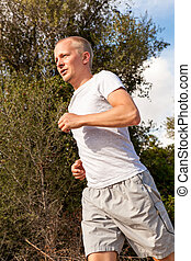 athletic man runner jogging in nature outdoor
