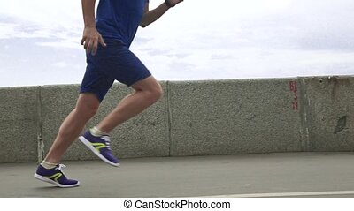 Athletic man running against river bank parapet and sky....