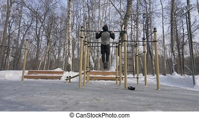 Athletic man training pull up exercise on winter gym workout...