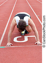 Athletic man waiting in starting block
