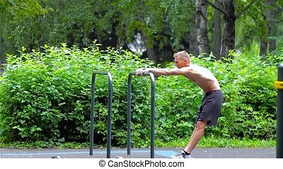 Athletic man warming up in City Park. side view. Workout.