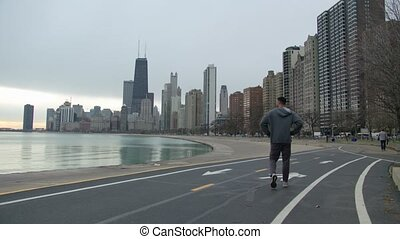 Athletic man with fit muscular body is resting after the running on the running track. Stops and taking a look at the sea. Chicago downtown and sea on the background.