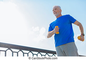Athletic man working out with dumbbells on the bridge