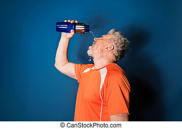 Athletic mature man in sportswear pouring water from sports bottle on face