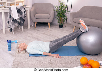 Athletic senior woman stretching her legs