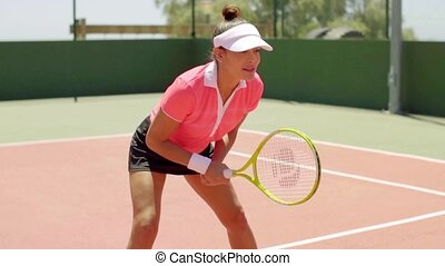 Athletic shapely woman playing a game of tennis