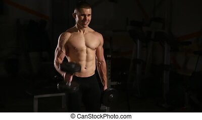 Athletic shirtless young sports man - fitness model holds the dumbbell in gym. Close-up