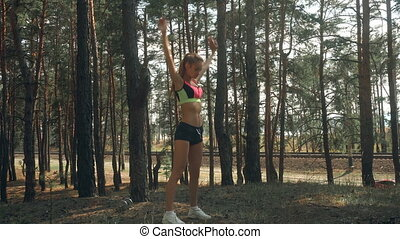Athletic slender girl in bright plumage makes workout in the...
