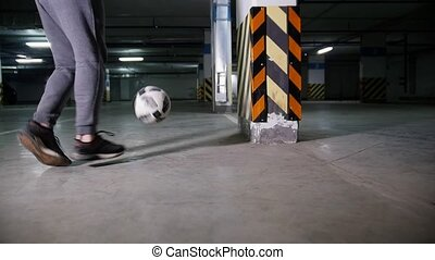 Athletic soccer man playing football on underground parking....