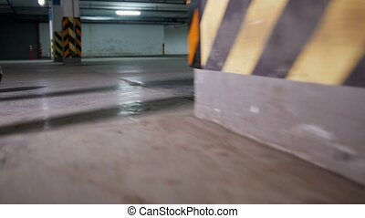 Athletic soccer man playing football on underground parking lot. Back view