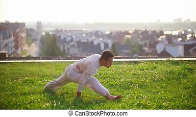 Athletic sports man sits on a twine on the grass in the summer