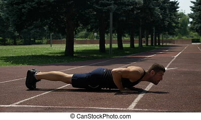 Athletic sportsman doing pushups on running track