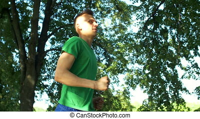 Athletic sporty young man jogging in public park