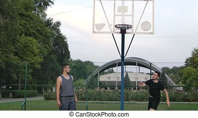 Athletic streetball player making attempt to score field goals during playing basketball on outdoor court. Close up. Slow motion