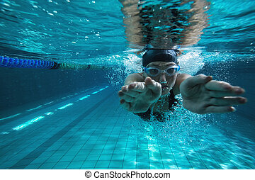 Athletic swimmer training on her own in the swimming pool at...