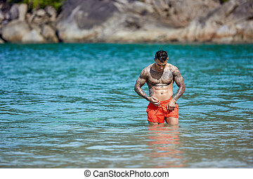 Athletic tattooed guy walking through the water at the tropical beach