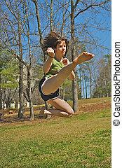 Athletic teen martial artist perform jump kick