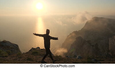 Athletic tourist girl in a bandana walks along the edge of a high cliff and spreads her arms to the side from pleasure over the Black Sea against the backdrop of a charming sunset in the warm autumn.