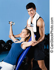 Athletic trainer helps woman to exercise with weights