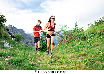 Athletic trainer measures the time of an athlete female race woman in the mountain