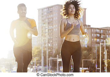 athletic woman and sports man running at sunset