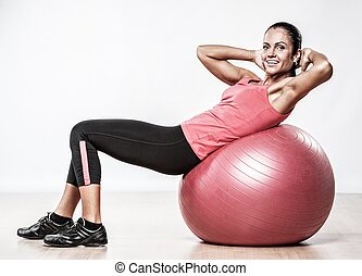 Athletic woman doing exercise on a fitness ball