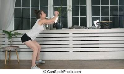 Athletic woman doing squats indoors - 4k footage. Cute young...
