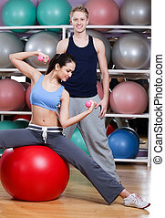 Athletic woman exercises in fitness gym with couch