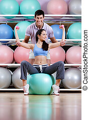 Athletic woman exercises in fitness gym
