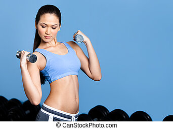 Athletic woman exercises with dumbbells