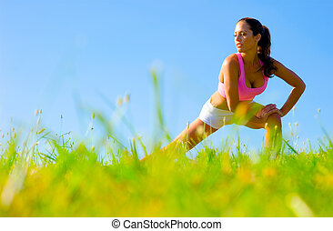 Athletic woman working out in a meadow, from a complete series of photos.