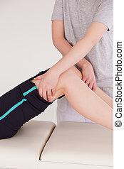 Athletic woman having a leg massage
